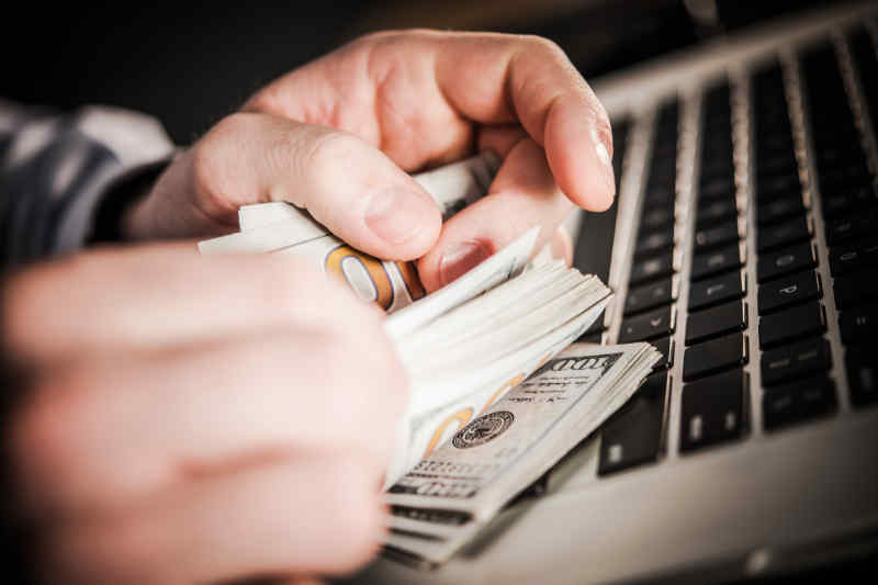 man counting money from website