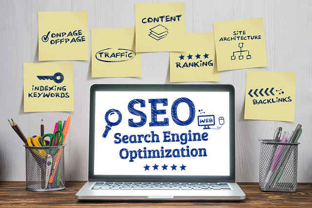 SEO and Search Engine Optimization displayed on a computer screen with digital marketing phrases posted on notes on the wall behind it.